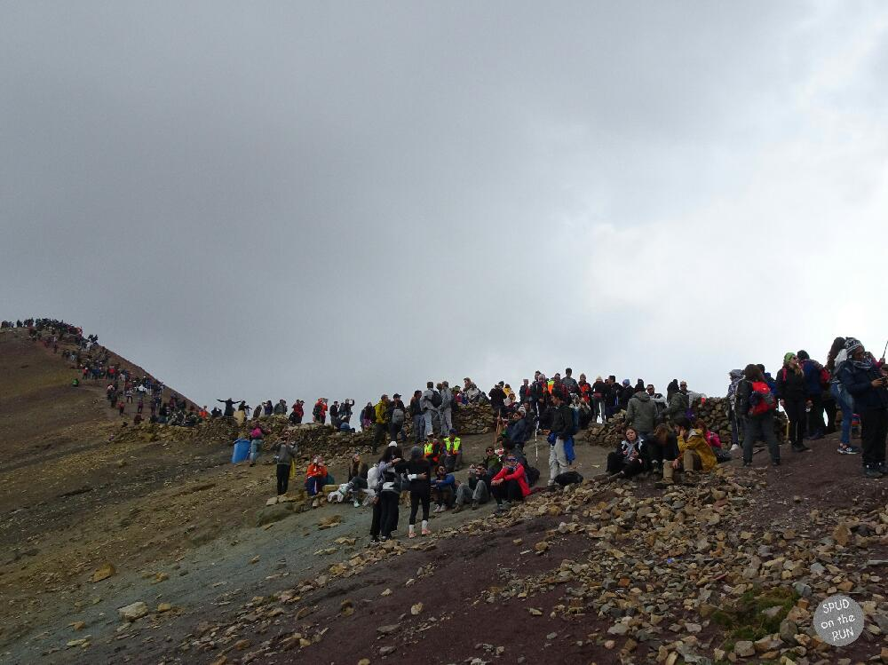 A mass of people walking up to the summit of Rainbow Mountain